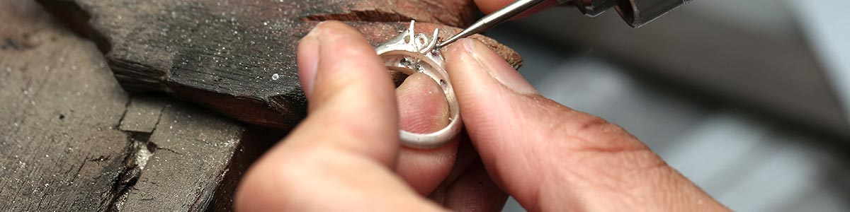 a man holding ring in a jewelry factory